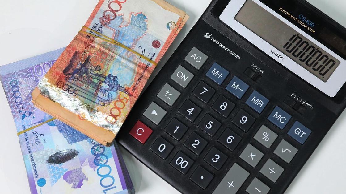 Калькулятор и две пачки денег лежат на столе