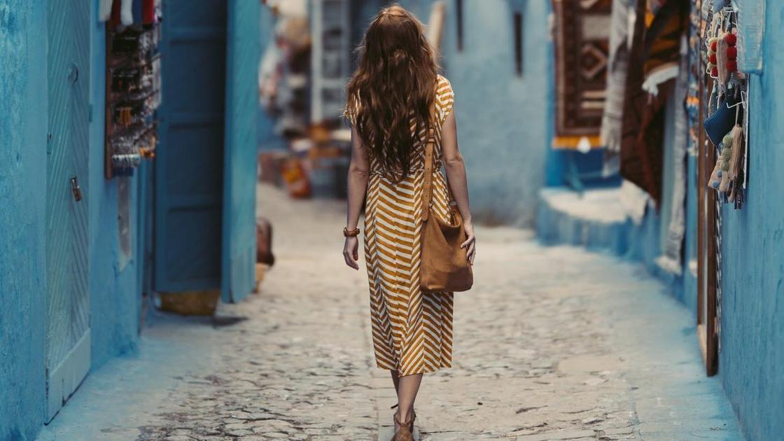 Девушка идет по улице синего города в Марокко