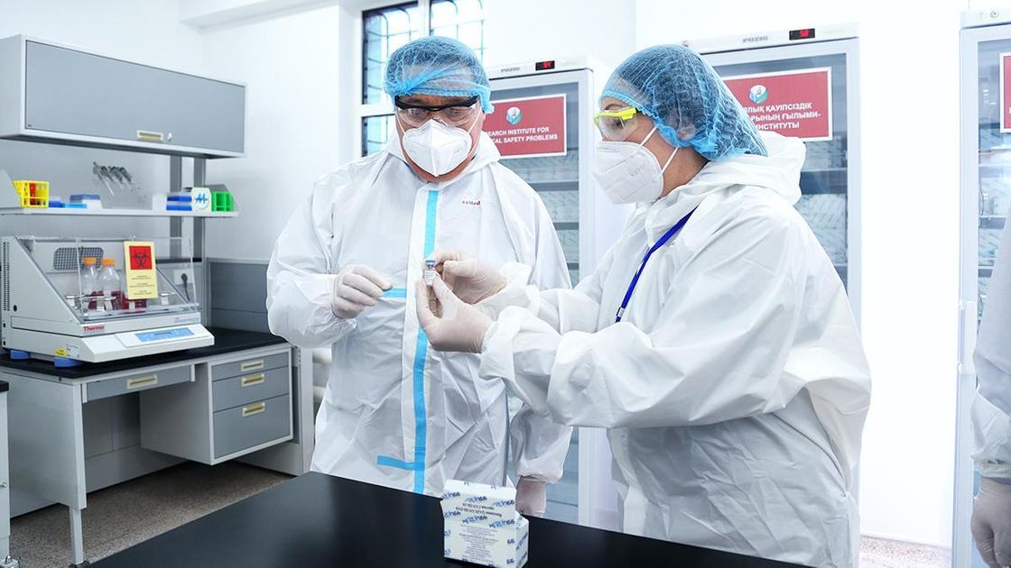 Медработники держат в руках ампулу с вакциной