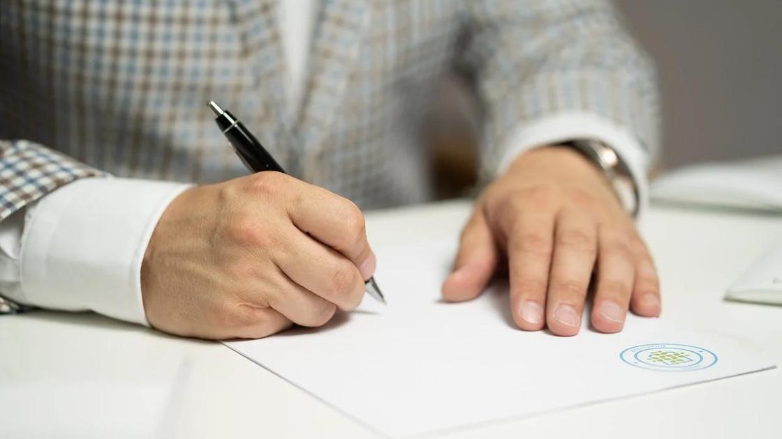 Мужчина подписывает документ с печатью
