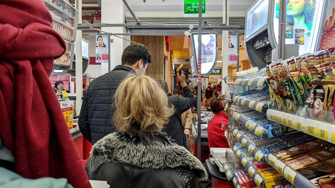 Люди стоят в очереди в магазине