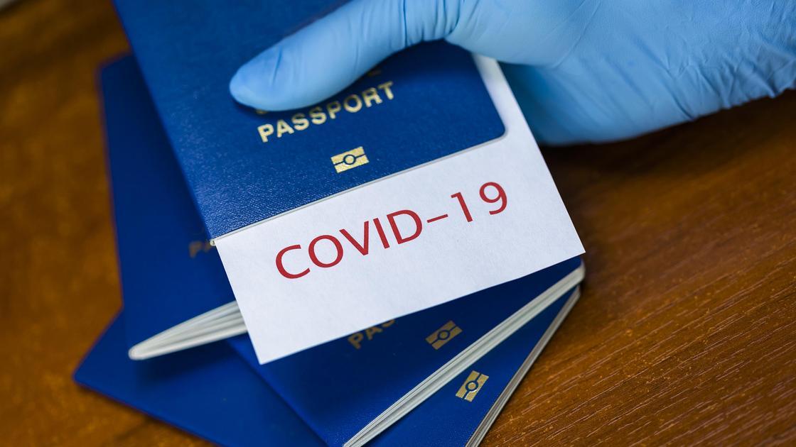 "Рука в перчатке держит паспорт с листком, на котором написано ""COVID-19"""