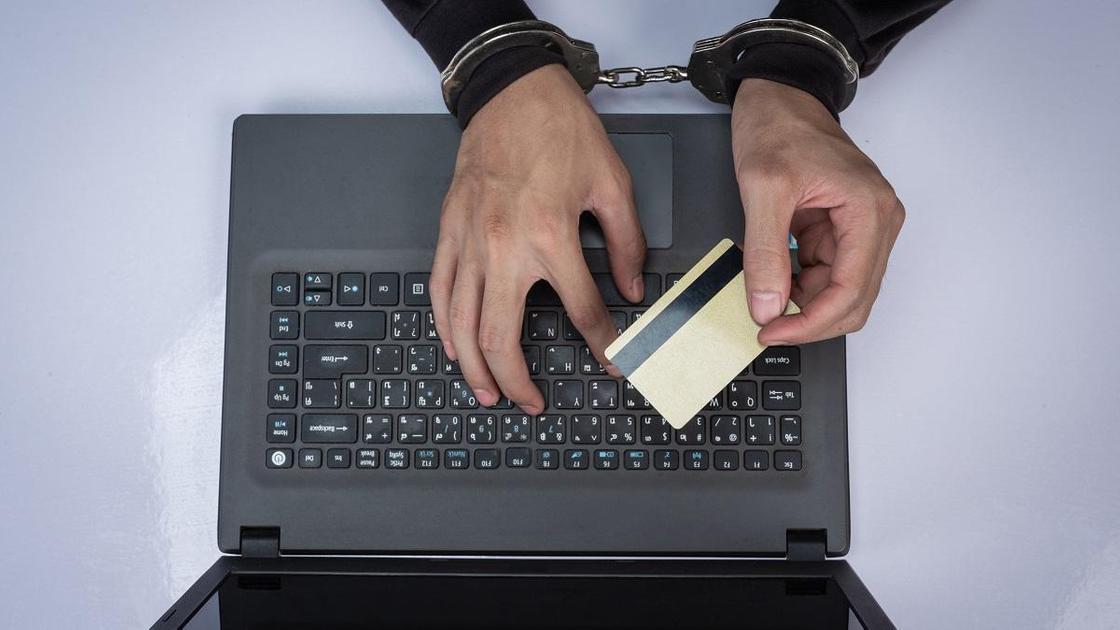 Мужчина в наручниках держит банковскую карту