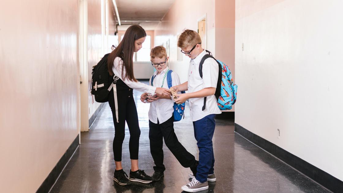 Дети стоят в коридоре школы
