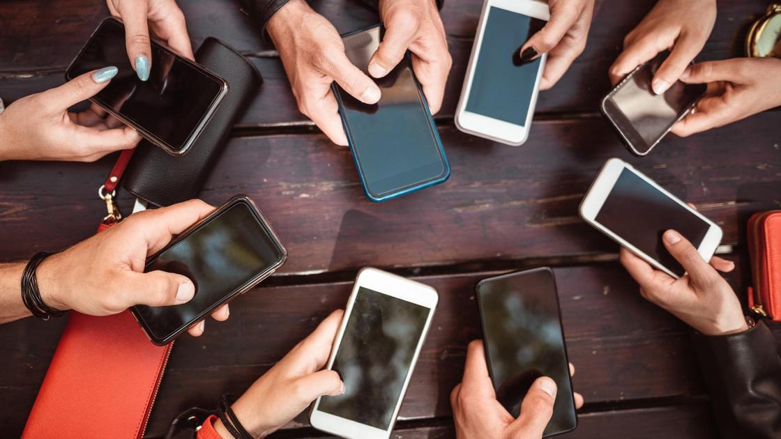Много людей держат в руках смартфоны