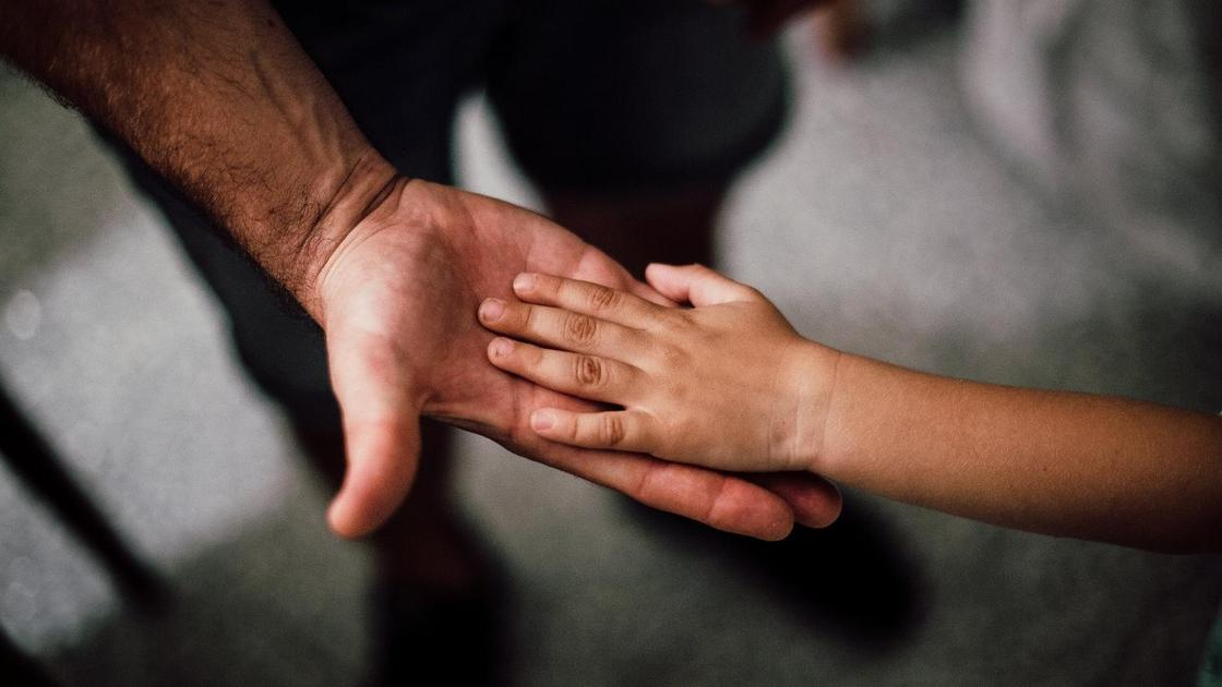 Ребенок положил руку на ладонь отца