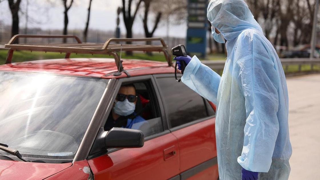 Медик в защитном костюме замеряет температуру