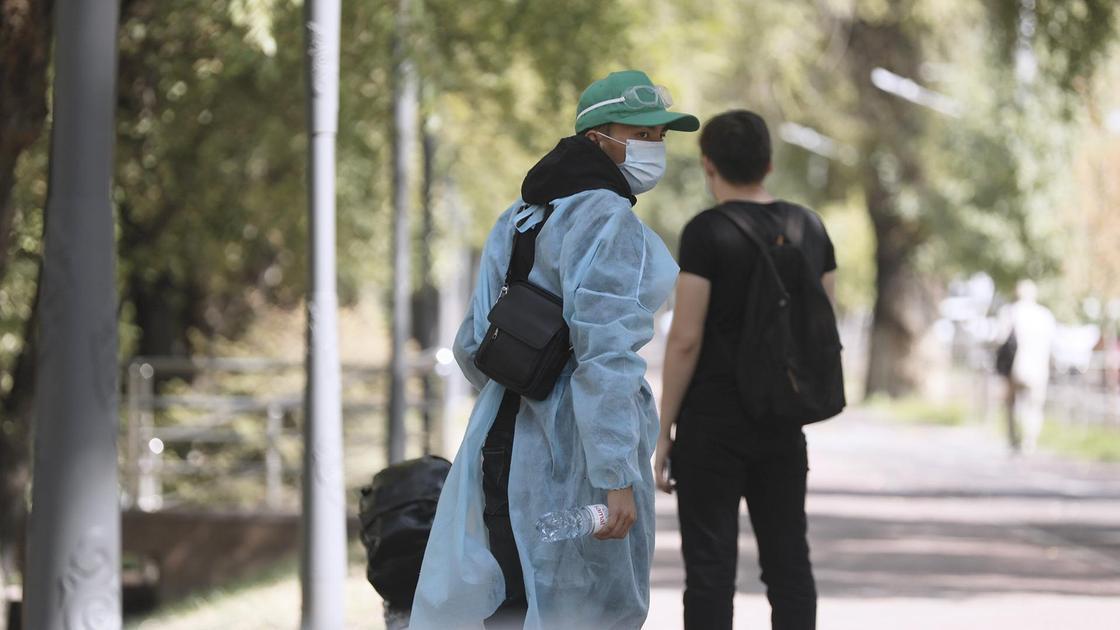 Женщина в защитной одежде и в маске на фоне парня на улице