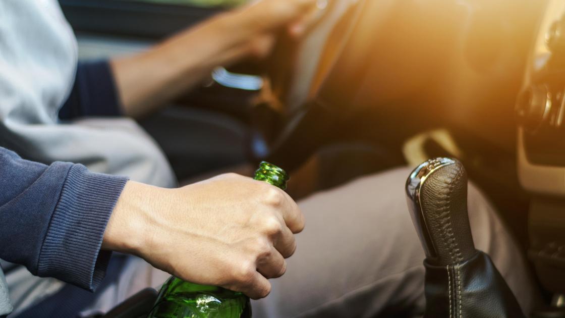 Мужчина на водительском сидении авто с бутылкой пива в руке