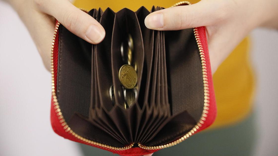 Женщина держит в руках кошелек с мелочью