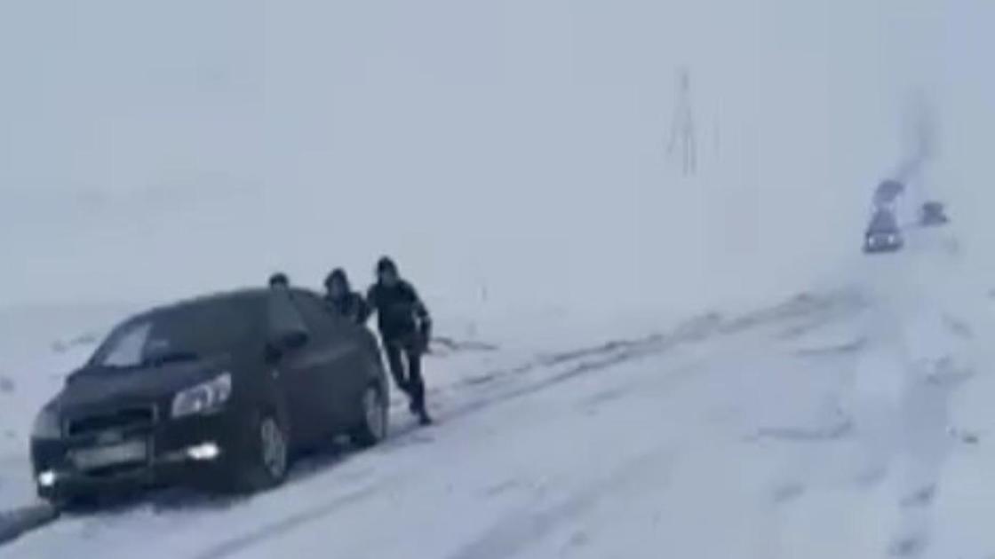 Мужчины толкают машину на заснеженной трассе