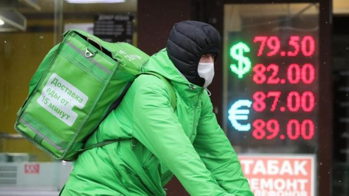 Курье на фоне рекламы с курсом валют