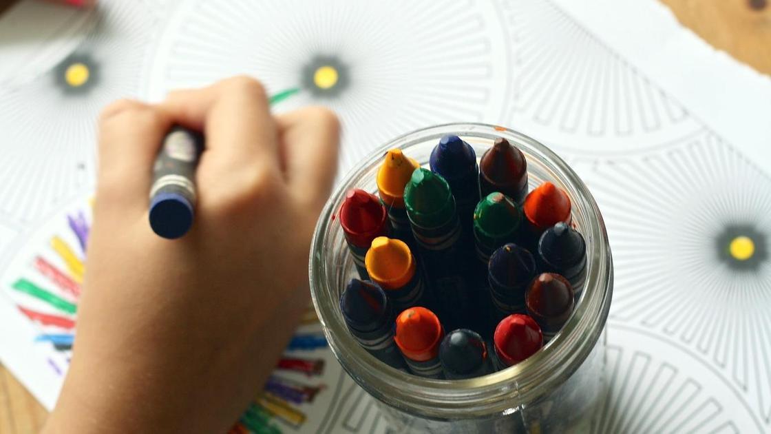 Ребенок рисует мелком на бумаге