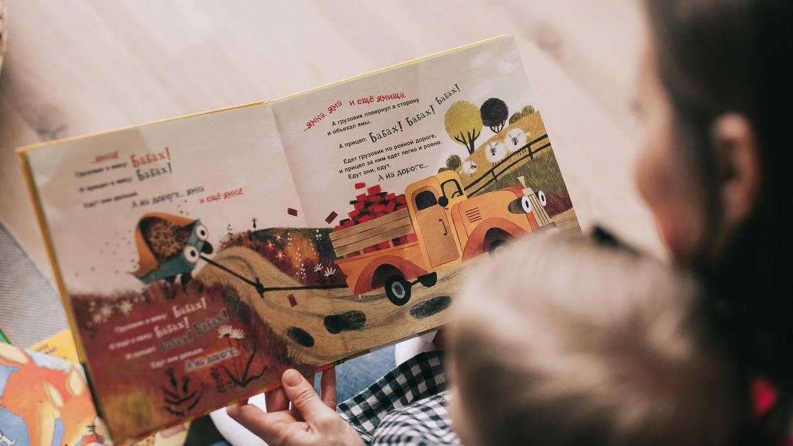 Женщина читает книгу ребенку
