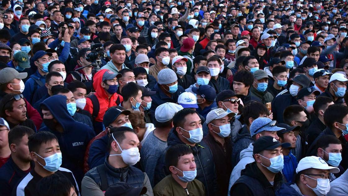 Толпа людей устраивает митинг в Бишкеке