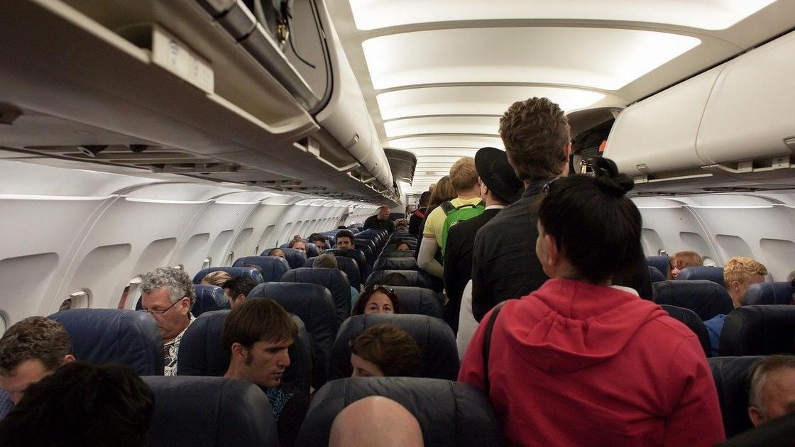 Пассажиры стоят в проходе на борту самолета