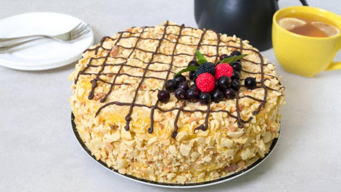 Торт «Наполеон», украшенный ягодами, в тарелке, рядом с чашкой чая