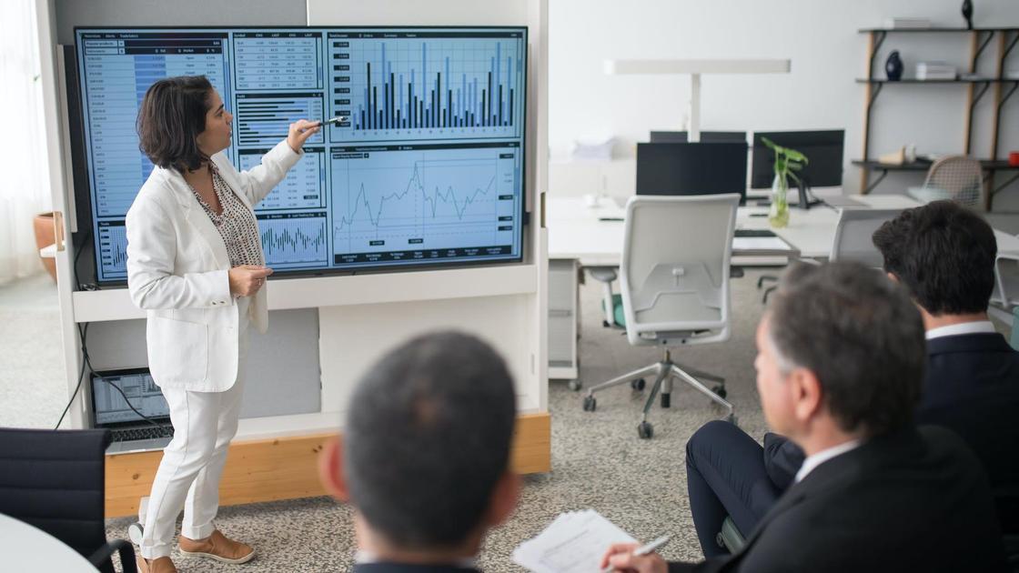 Женщина в белом костюме делает доклад по диаграммам на экране для мужчин в деловых костюмах