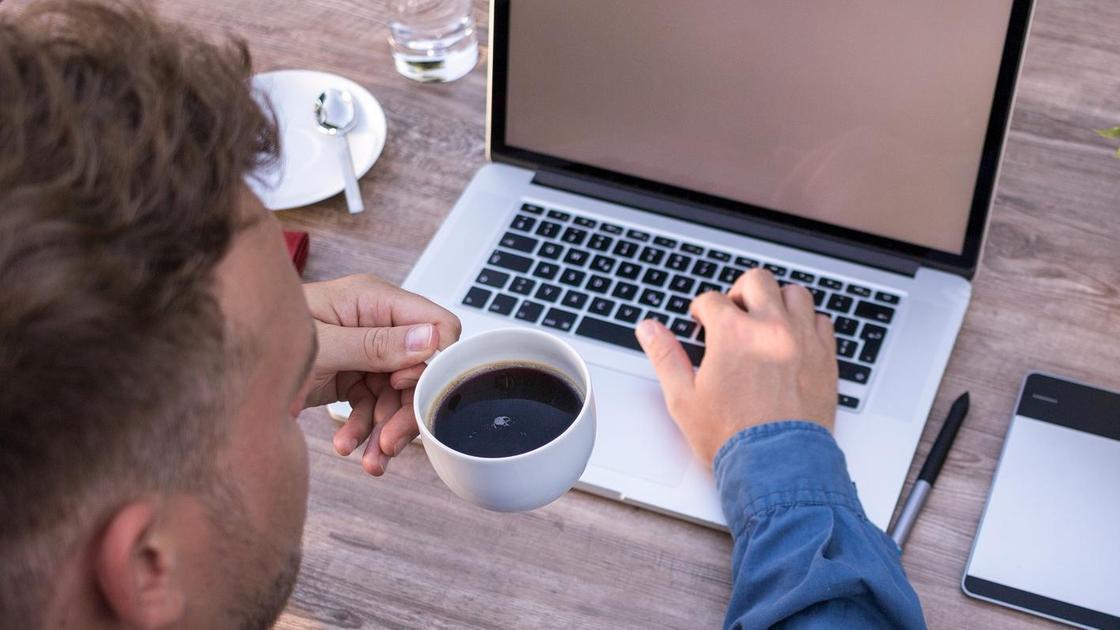 Мужчина держит кружку с кофе перед компьютером