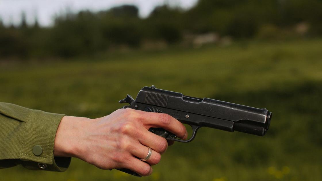 Мужчина держит в руках пистолет