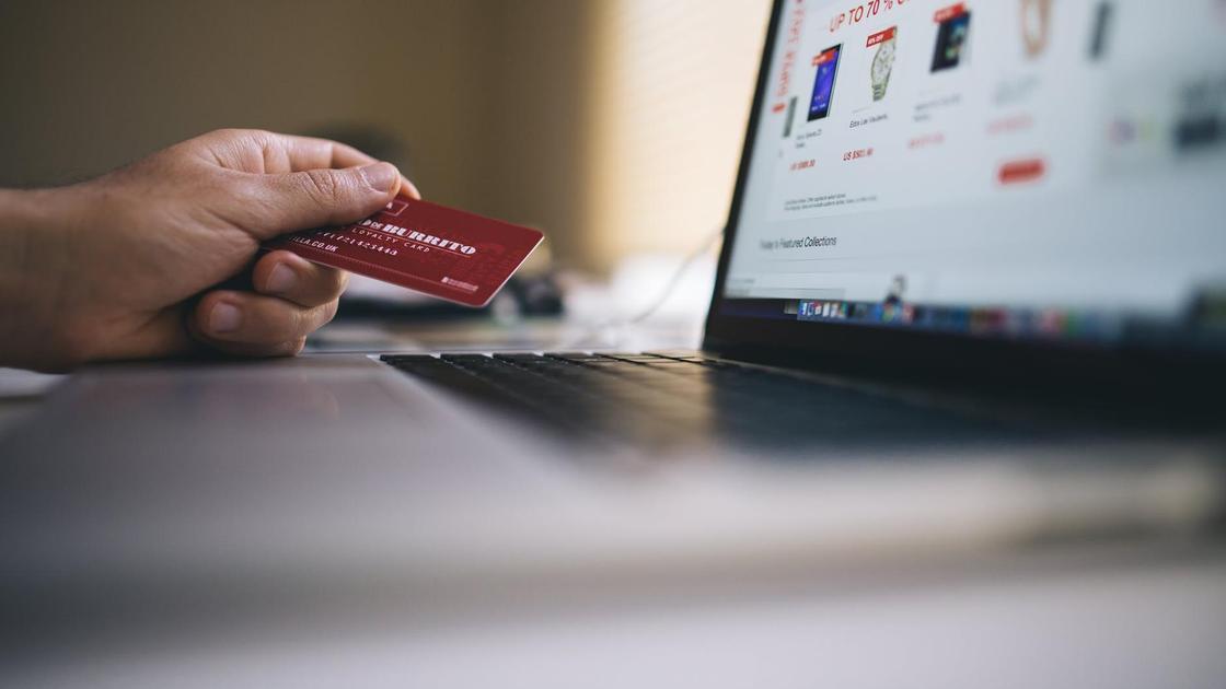 Человек смотрит в монитор и покупает товары онлайн