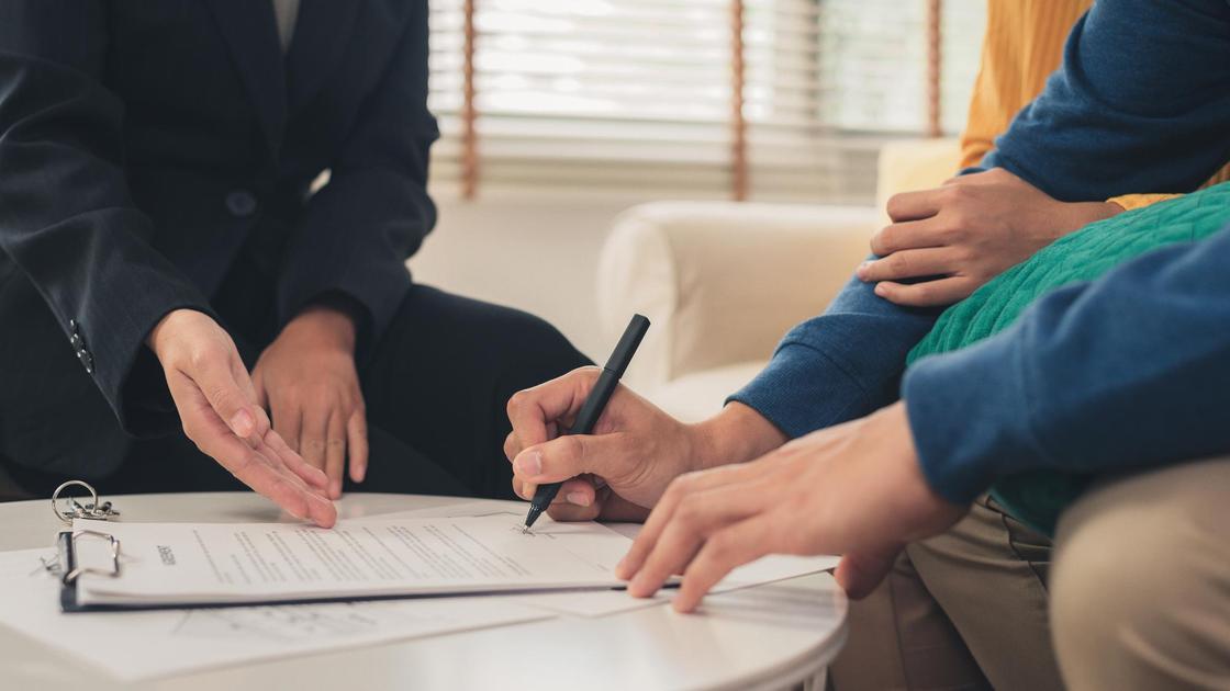 Мужчина и женщина подписывают договор