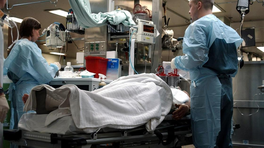 врачи стоят возле больного в палате больницы