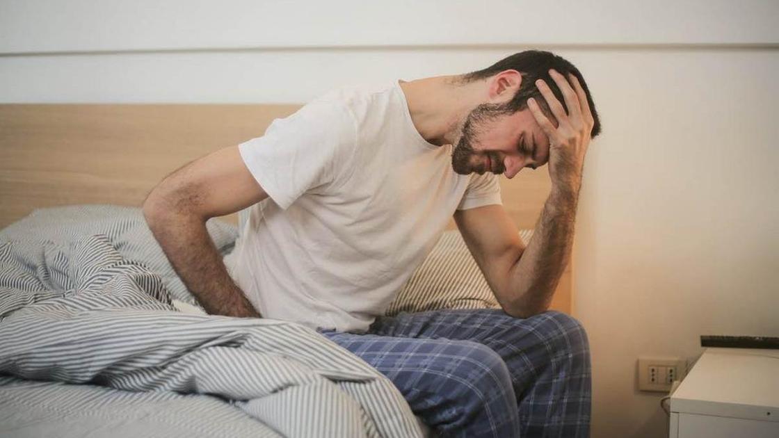 Мужчина в пижаме на кровати, держась рукой за голову