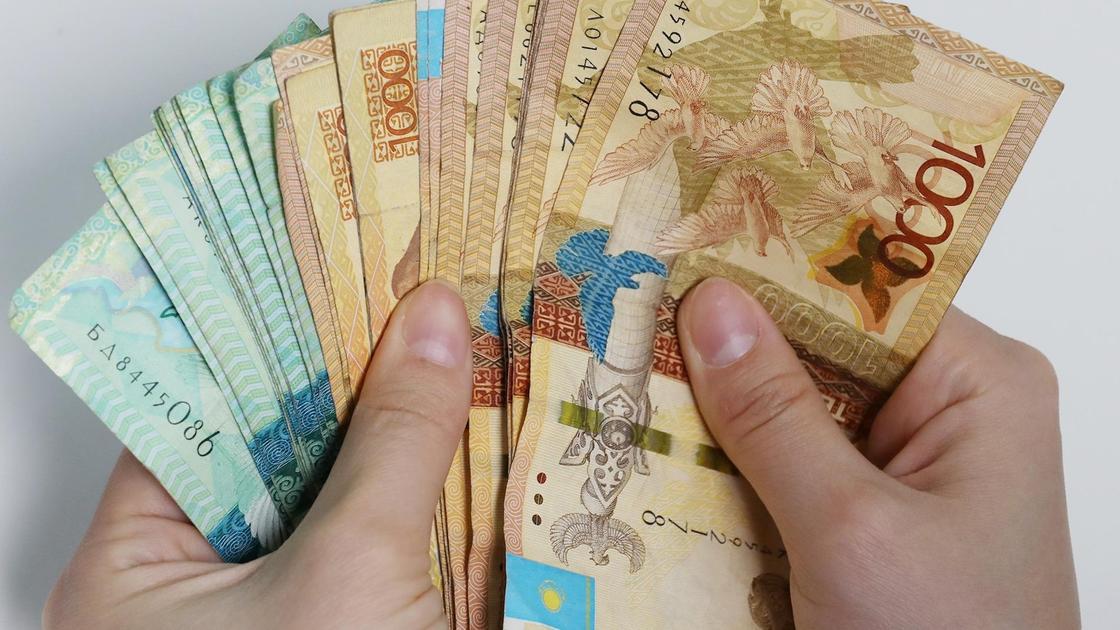 мужчина держит пачку денег в руках