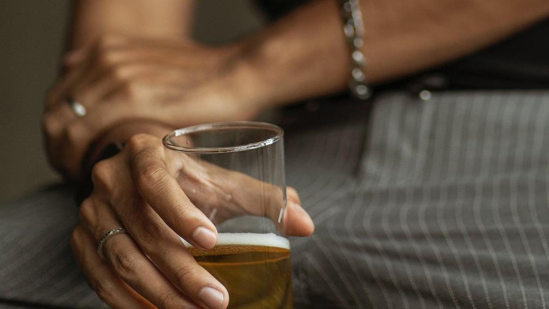 Мужчина держит стакан в руке