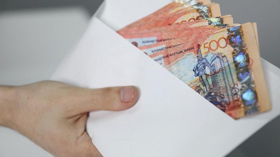 Мужчина держит в руках конверт с деньгами