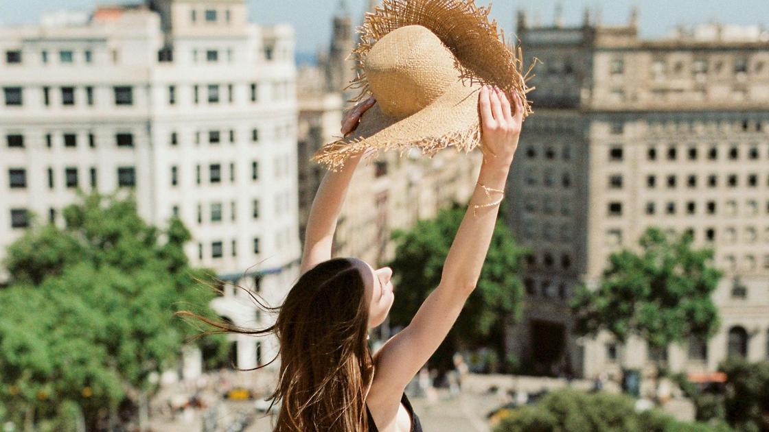 Девушка прикрывается шляпой от солнца