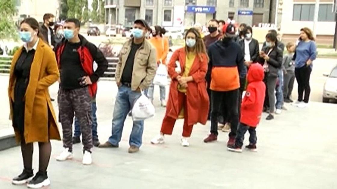 Люди стоят в очередях у торговых домов после смягчения карантина в Актобе