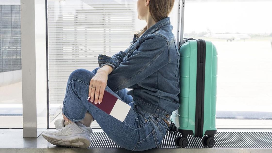 Женщина ждет рейс в аэропорту