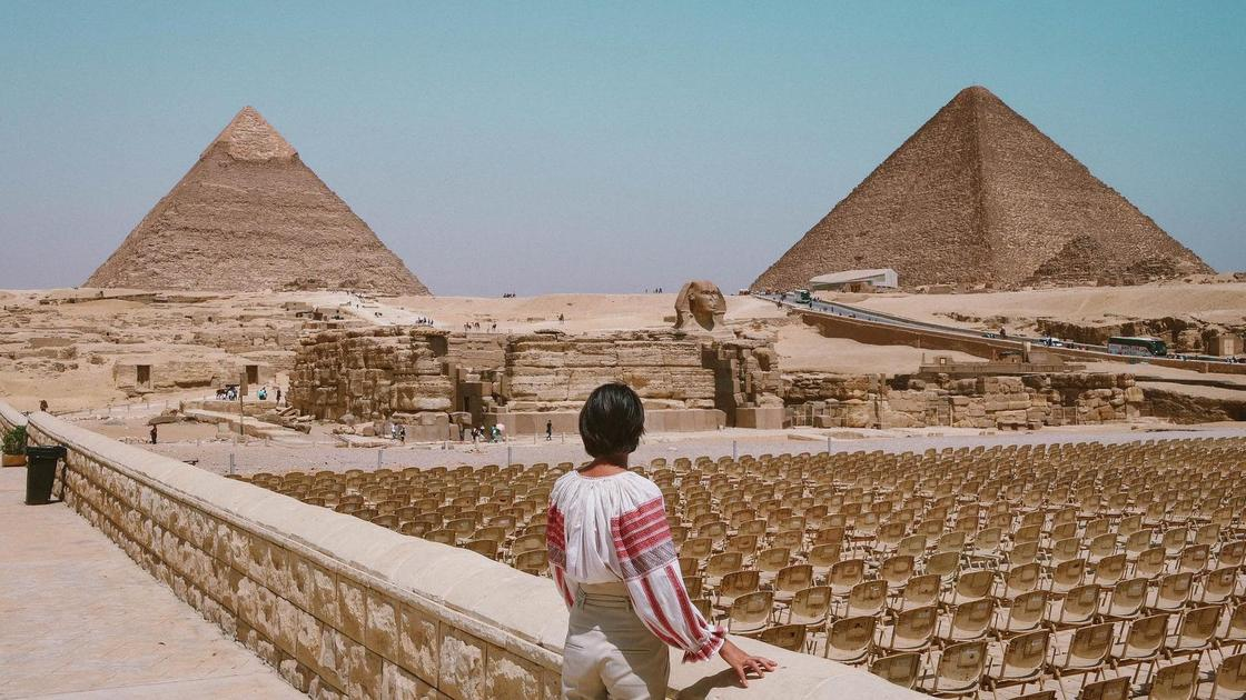 Девушка смотрит на пирамиды в Египте