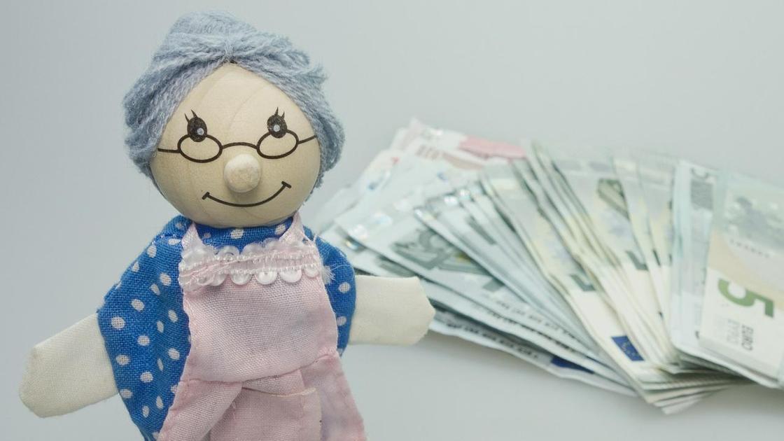 Игрушечная бабушка стоит на столе рядом с деньгами