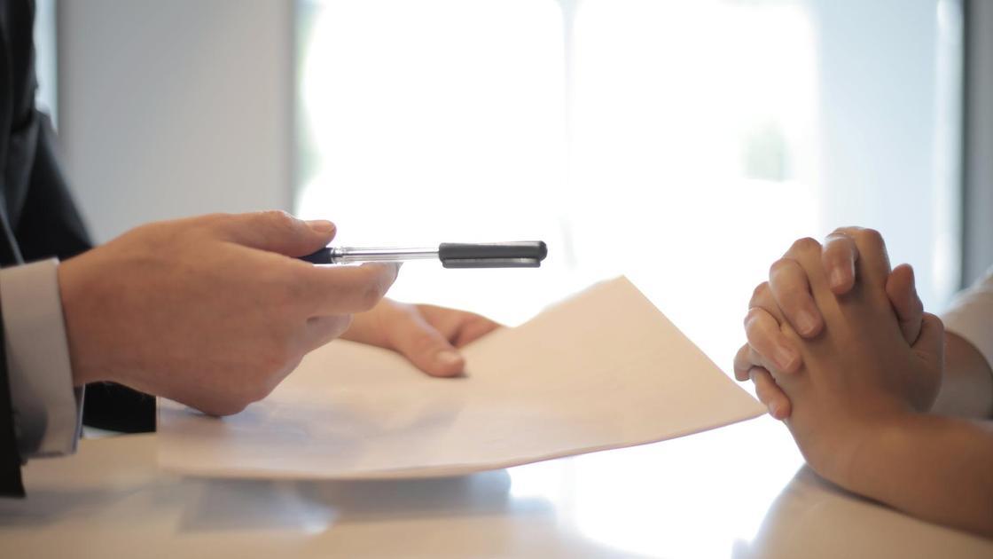 Мужчина дает женщине листок и бумагу для подписания