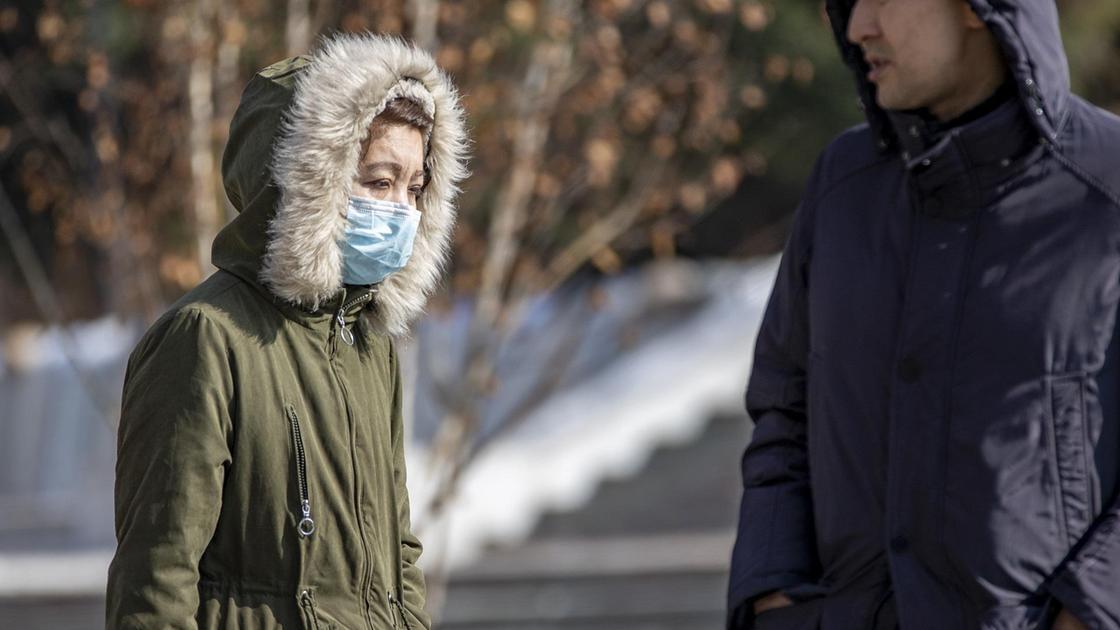 Женщина в куртке и маске