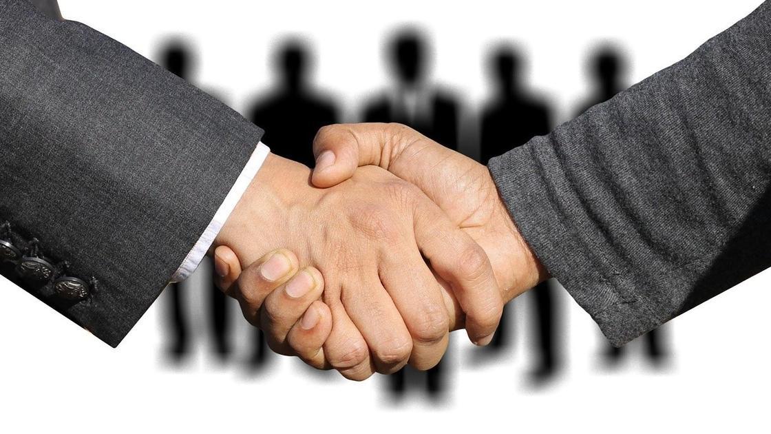 Рукопожатие на фоне фигур людей