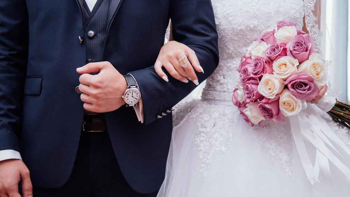 невеста держит под руку жениха