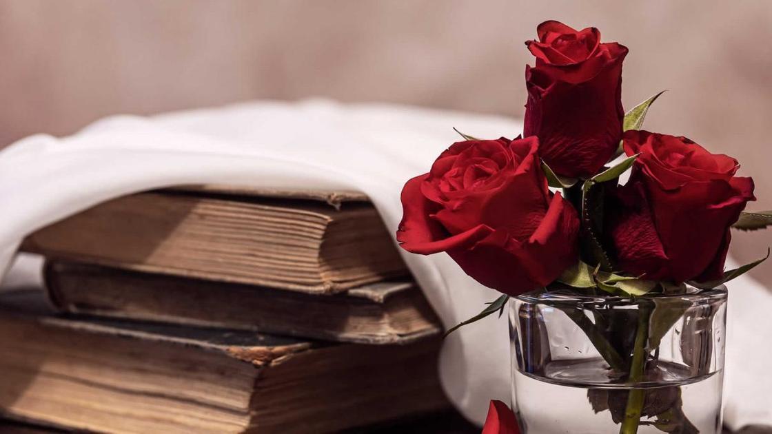 Книги, красные розы в стакане
