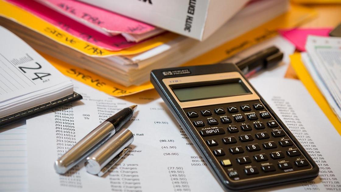 Калькулятор лежит на столе среди бумаг