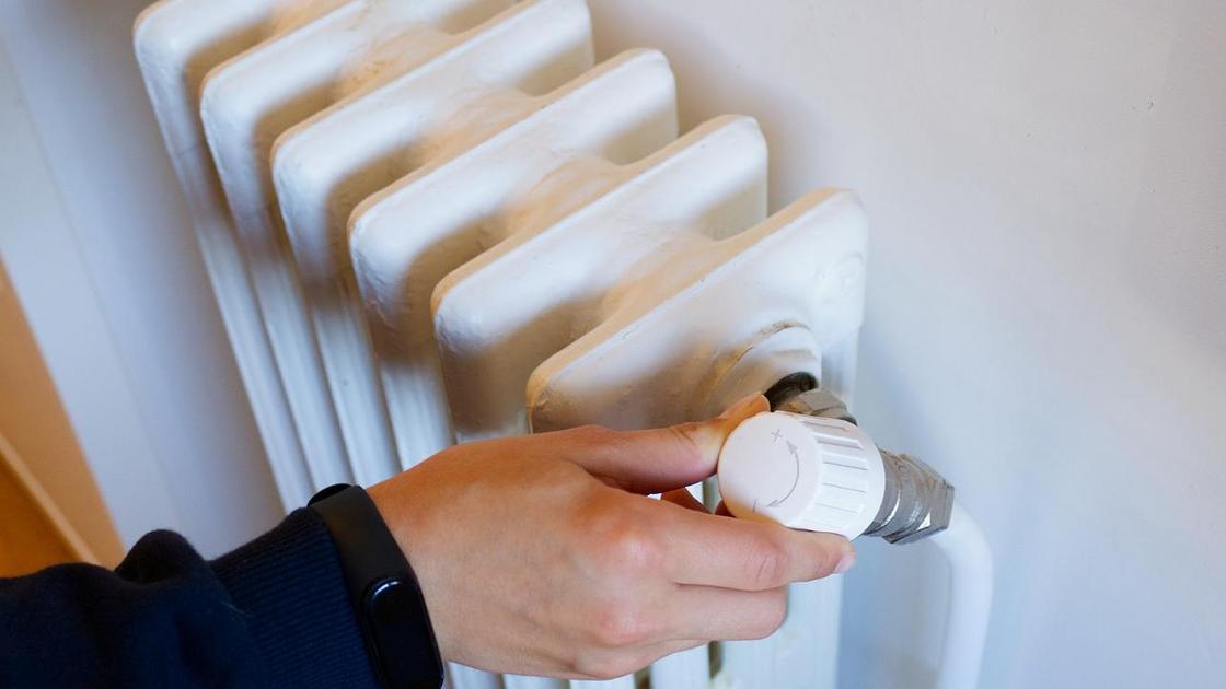Мужчина регулирует радиатор
