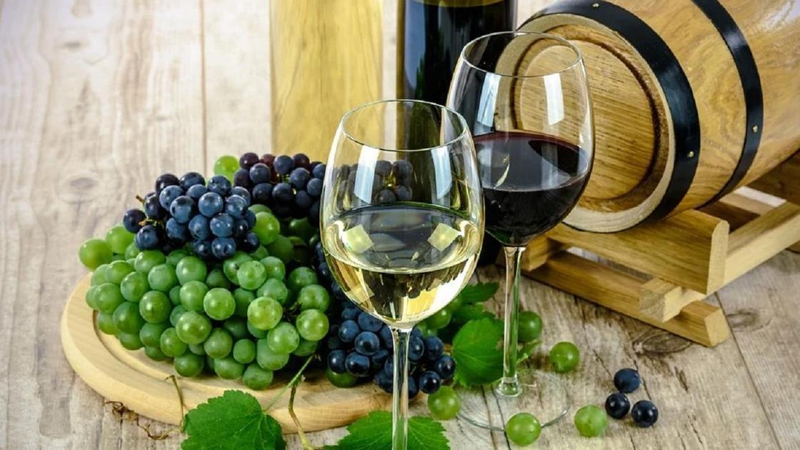 Бокалы с красным и белым вином на фоне винограда и бочонка