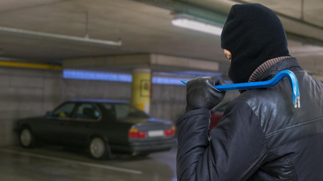 Мужчина в куртке и балаклаве идет по парковке с синей монтировкой на плече