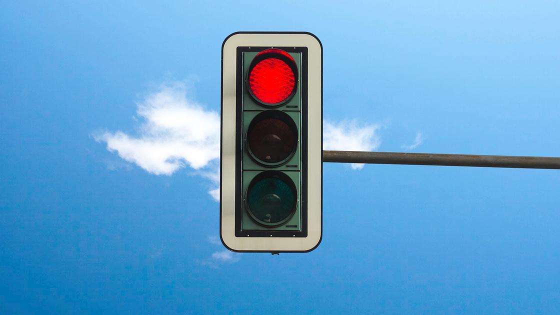 Светофор с горящим красным сигналом установлен на поперечной трубе
