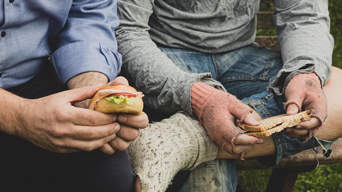 Нищий человек и человек с достатком едят сэндвичи