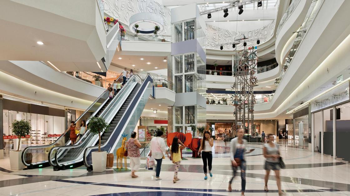 Посетители торгового центра идут по своим делам