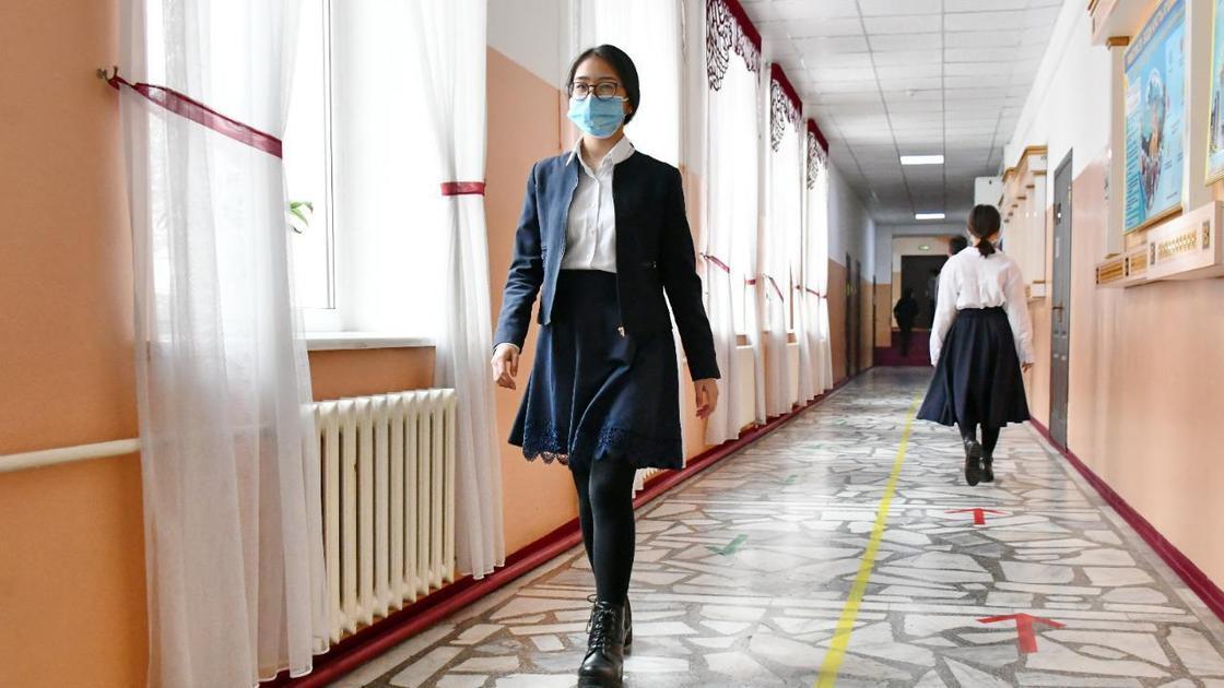 Школьница идет по коридору