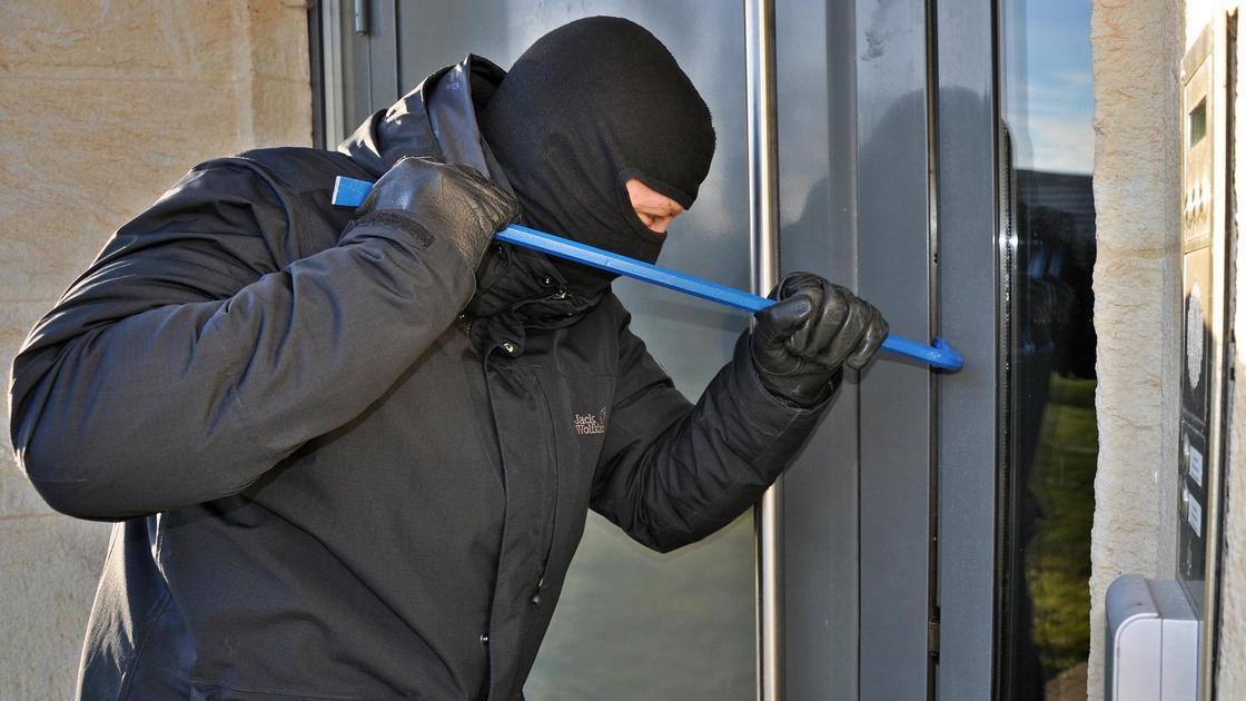 Мужчина в черном взламывает дверь с помощью монтировки